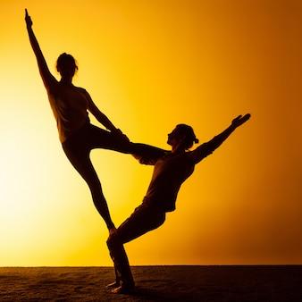 Übendes yoga von zwei leuten im sonnenunterganglicht