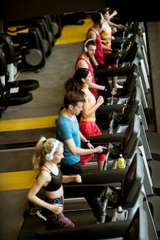 Über ansicht an der gruppe jungen leuten, die auf tretmühlen in der modernen sportturnhalle laufen
