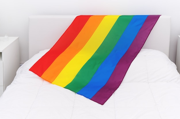 Über ansicht der regenbogenflagge lgbt-gemeinschaft auf weißem bett