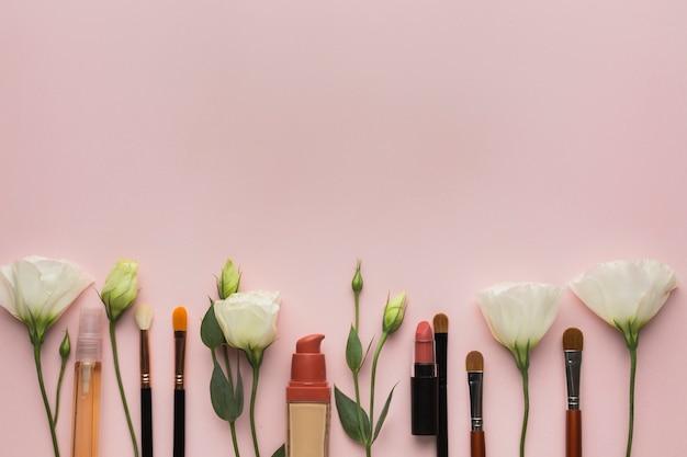 Über ansichtanordnung mit make-up und blumen