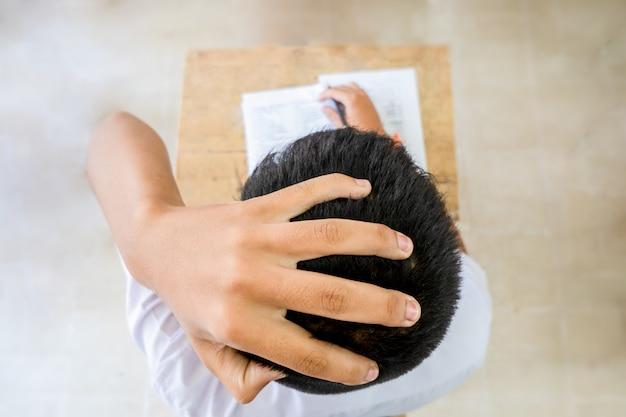 Über ansichthand auf kopferscheinenkopfschmerzen des studenten langweilte das lernen und die testprüfung