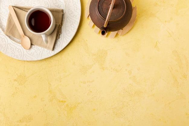 Über ansichtrahmen mit teekanne auf gelbem hintergrund