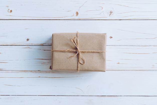 Über brauner geschenkbox auf holztischhintergrund mit kopienraum.