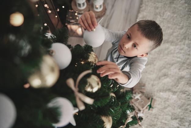 Über dem jungen im schlafanzug, der einen feiertagsbaum vorbereitet