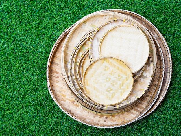 Über dem satz von bambuswebschalen, behälter zum platzieren von thailändischem essen vieler größen isoliert auf grünem gras.
