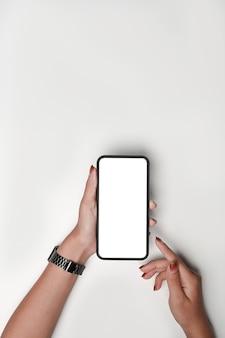 Über der ansicht frau, die mock-up-meile-telefon auf weißem tisch hält.