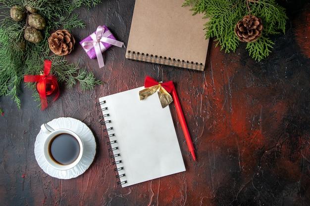 Über der ansicht von tannenzweigen eine tasse schwarztee-dekorationszubehör und ein geschenk neben einem notizbuch mit stift auf dunklem hintergrundmaterial