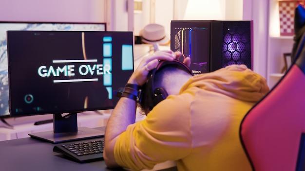 Über der schulter aufnahmen eines mannes, der professionelle videospiele in einem raum mit bunten neonlichtern spielt.