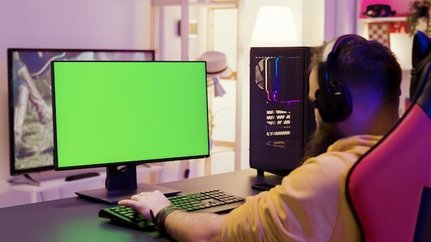 Über der schulter aufnahmen eines mannes, der videospiele auf einem computer mit grünem bildschirm spielt. professioneller spieler.