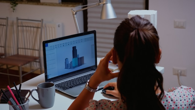 Über die schulter geschossen von einem ingenieur, der mit cad-software auf einem desktop-computer arbeitet. designer, der ein 3d-konzept von gebäuden verwendet, die von zu hause aus überstunden machen, um ein neues modernes modell zu erstellen und zu studieren