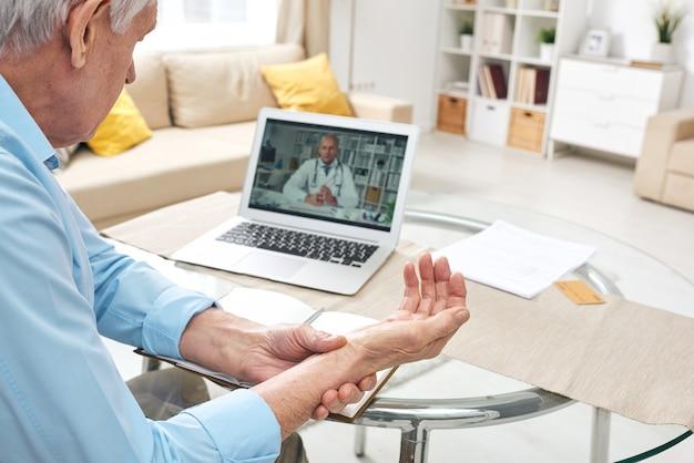 Über die schulteransicht des älteren mannes, der am tisch sitzt und puls während der online-konsultation mit dem arzt prüft