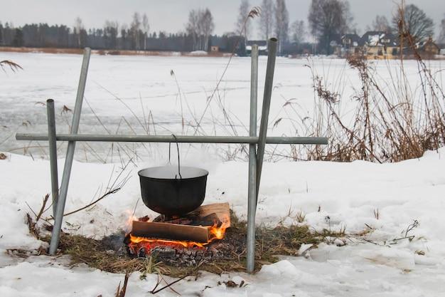 Über einem feuer gibt es einen topf, essen, im winter bei einer wanderung am kleinen fluss