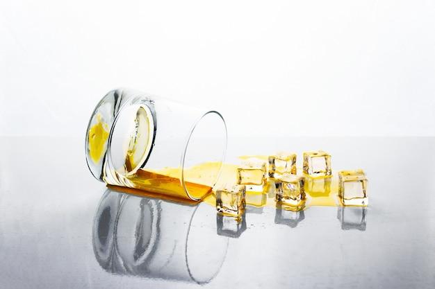 Über glas goldenen alkohols mit eiswürfeln auf weißer reflektierender oberfläche, whisky oder cognac geklopft.
