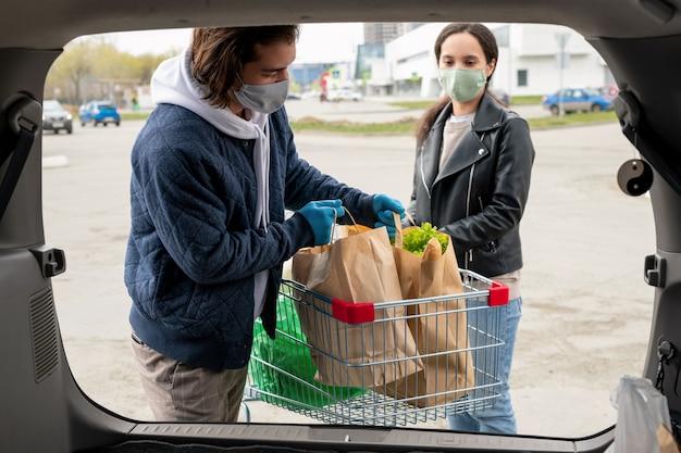 Über kofferraumansicht des jungen paares in masken, die taschen in kofferraum nach supermarkteinkauf laden
