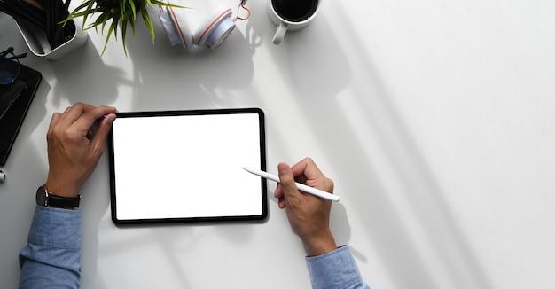 Über kopfaufnahme eines grafikdesigners mit stift, der auf grafiktablett mit leerem bildschirm schreibt.