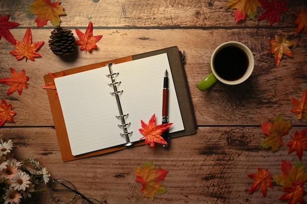 Über leerem notizbuch, kaffeetasse und herbstahornblättern auf hölzernem hintergrund.