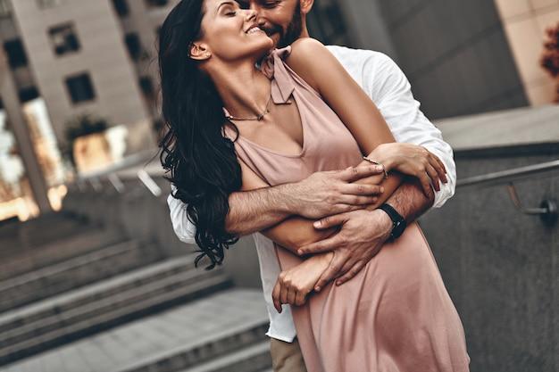Über liebe flüstern. hübscher junger mann, der seine schöne freundin umarmt, während er zeit zusammen in der stadt verbringt