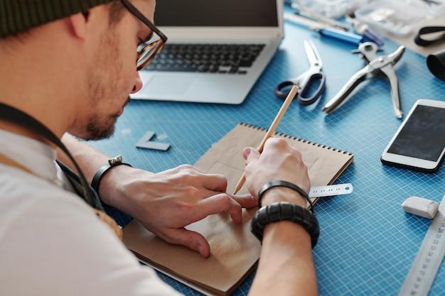 Über schulteransicht des beschäftigten jungen mannes, der entwurf des lederprodukts am tisch zeichnet