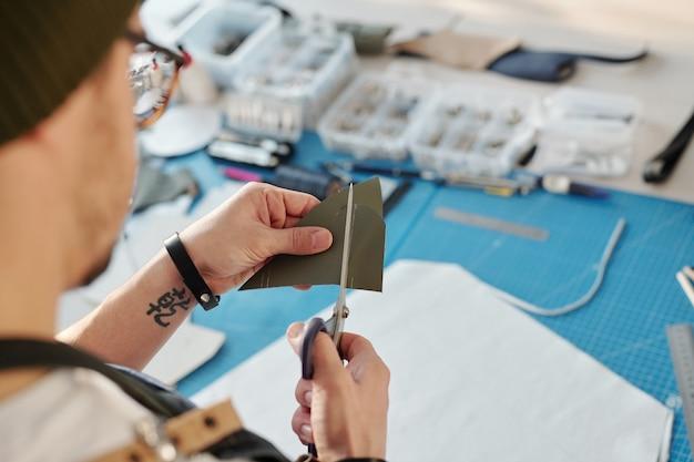 Über schulteransicht des handwerkers mit tätowierungsschneidlederstück mit schere in der werkstatt