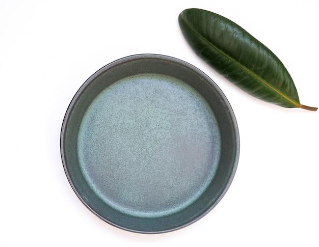 Über teller zum essen, leeren raum in kreisförmigen schüssel und grünen blättern