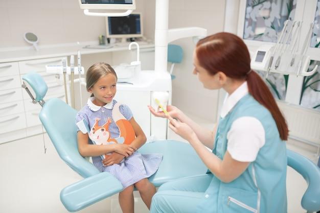 Über zähne erzählen. draufsicht eines mädchens, das zahnarzt anschaut und über zähne und zahnpflege erzählt