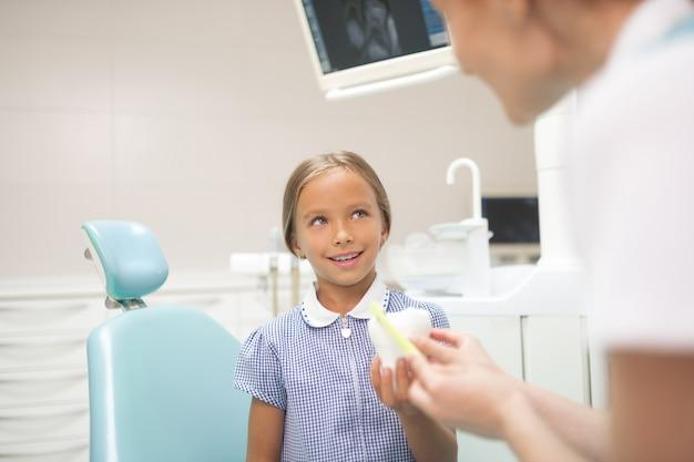 Über zahngesundheit. kinderzahnarzt, der mädchen über zahngesundheit und zahnpflege erzählt