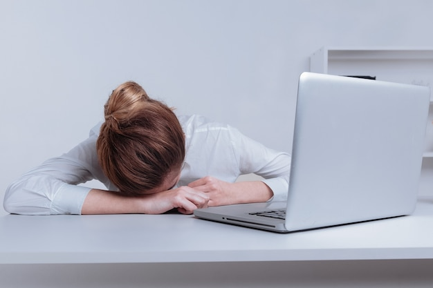 Überarbeitet und müde beim schlafen über einem laptop in einem schreibtisch bei der arbeit in ihrem büro