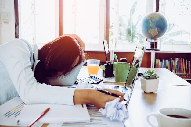 Überarbeitet und müde junge frau schläft auf dem schreibtisch