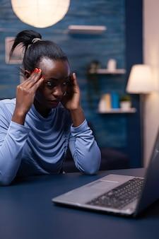 Überarbeitete afrikanische geschäftsfrau, die kopfschmerzen hat, während sie spät in der nacht vom home office aus arbeitet. müde, fokussierte mitarbeiter, die moderne drahtlose netzwerktechnologie verwenden und überstunden machen.