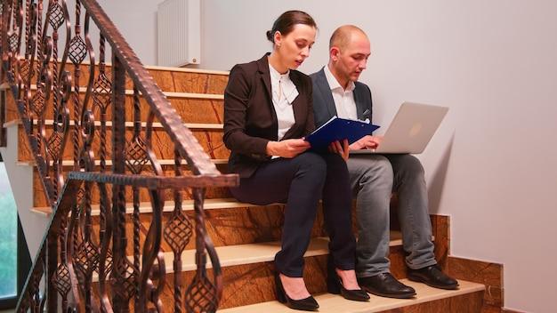 Überarbeitete erschöpfte geschäftsleute mit laptop, die an schwierigen fristen arbeiten, sitzen auf der treppe im bürogebäude. gruppe professioneller erfolgreicher geschäftsleute, die am finanzarbeitsplatz spazieren gehen.