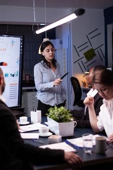 Überarbeitete, fokussierte, vielfältige geschäftsleute, die im büroraum für geschäftstreffen arbeiten