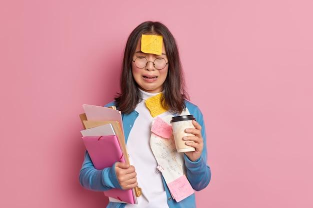 Überarbeitete frustrierte buchhalterin hat viel fernarbeit, umgeben von papierdokumenten, trinkt kaffee, um vor verzweiflung zu weinen.