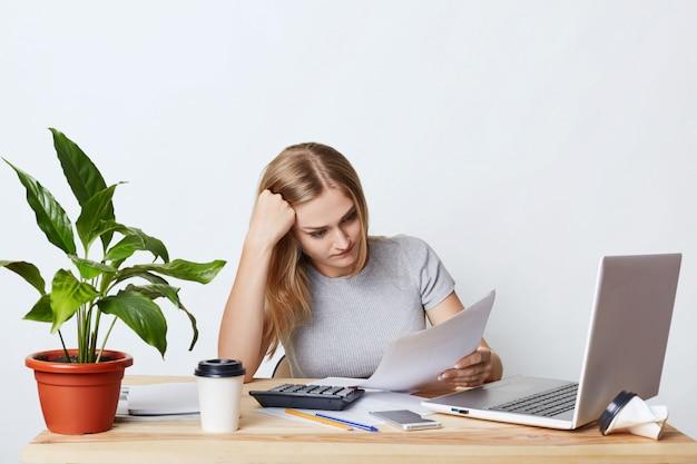Überarbeitete geschäftsfrau, die am holztisch sitzt, von modernen geräten umgeben ist, dokumente aufmerksam liest und versucht, alles zu verstehen. buchhalterin, die rechnungen und ausgaben berechnet