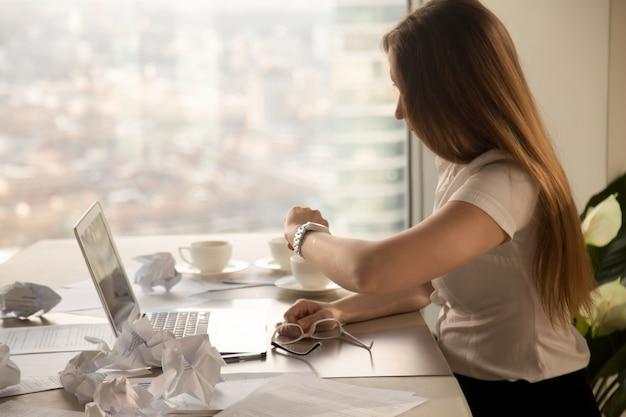 Überarbeitete geschäftsfrau, die armbanduhr, zeit überprüfend betrachtet, um frist einzuhalten