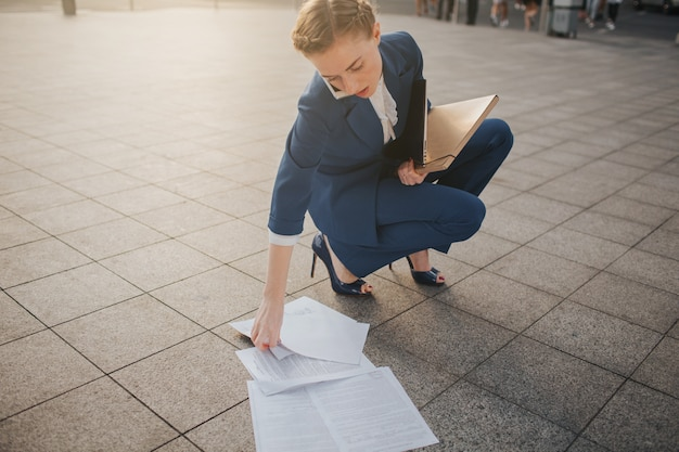 Überarbeitete geschäftsfrau, die viel papierkram hat. geschäftsfrau, umgeben von vielen papieren. geschäftsfrau, die im papierhaufen steht.