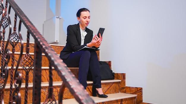 Überarbeitete geschäftsfrau, die während des videoanrufs über die projektfrist lächelt, die auf der treppe des firmengebäudes sitzt. unternehmer im gespräch mit dem kunden mit smartphone auf der treppe.