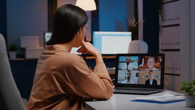 Überarbeitete geschäftsfrau diskutiert mit remote-partnern auf laptop