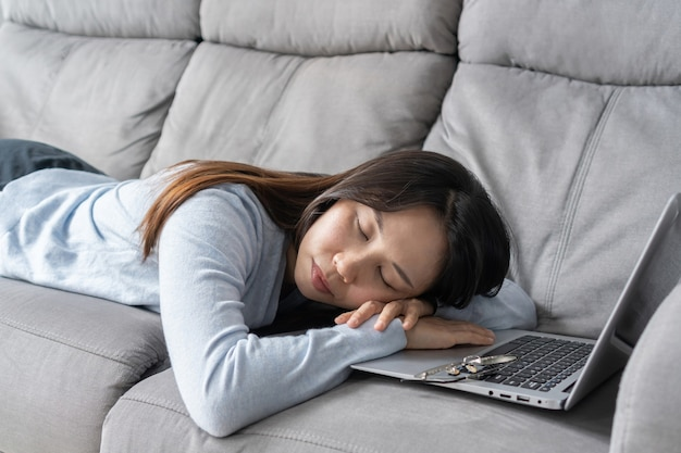 Überarbeitete gestresste asiatische geschäftsfrau ist am computer eingeschlafen. müder student, der auf sofa schläft fernunterricht. online-bildung oder arbeitskonzept.