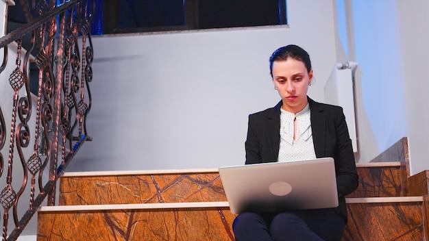 Überarbeitete gestresste geschäftsfrau, die spät abends an der geschäftsfrist auf dem laptop arbeitet. seriöser unternehmer, der im firmenjob sitzt und auf der treppe des geschäftsgebäudes sitzt.