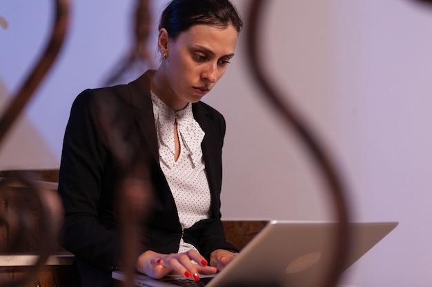 Überarbeitete gestresste geschäftsfrau, die spät am abend am geschäftstermin arbeitet. seriöser unternehmer, der an einem jobprojekt arbeitet, das nachts auf der treppe des geschäftsgebäudes sitzt, um zu arbeiten.