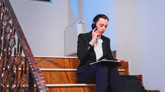 Überarbeitete müde geschäftsfrau, die während des telefonats die projektfrist liest, mit einem kollegen, der auf der treppe des geschäftsgebäudes sitzt. ernster unternehmer, der spät in der nacht an einem firmenjob arbeitet.