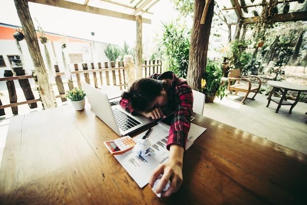 Überarbeitete und müde junge frau, die auf schreibtisch schläft
