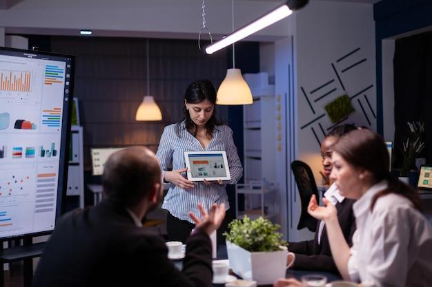 Überarbeitete workaholic-unternehmerin, die marketinggrafiken mit tablet-überarbeitung bei der unternehmenslösung spät in der nacht im besprechungsraum zeigt