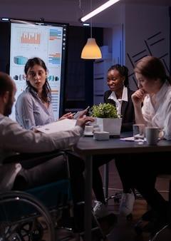 Überarbeiteter behinderter geschäftsmann im rollstuhl, der finanzpapiere-statistiken im besprechungsraum des geschäftsbüros teilt