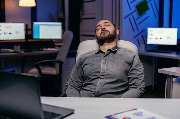 Überarbeiteter erschöpfter mann schläft auf stuhl im leeren büro. workaholic-mitarbeiter schläft ein, weil er spät nachts allein im büro für ein wichtiges unternehmensprojekt arbeitet.
