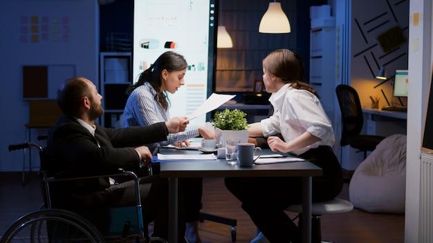 Überarbeiteter gelähmter behinderter unternehmer im rollstuhl, der am schreibtisch sitzt und in der firma überarbeitet ...