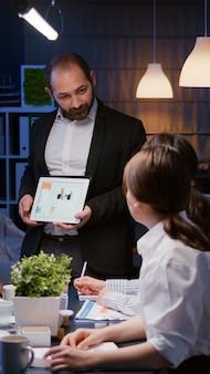 Überarbeiteter geschäftsmann, der finanzdiagramme mit tablet-brainstorming-firmenidee zeigt...
