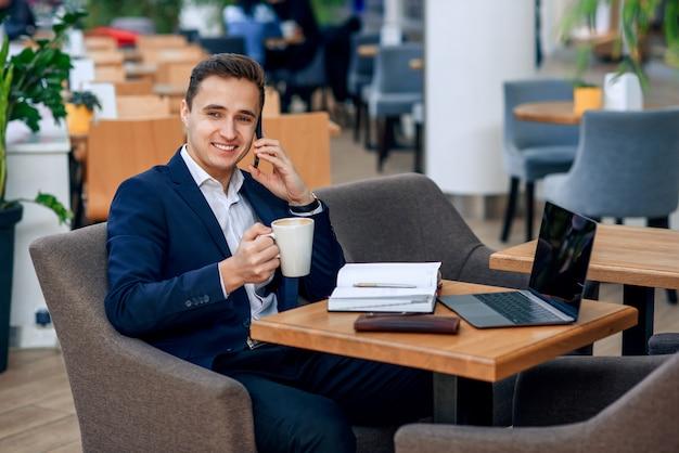 Überarbeiteter geschäftsmann hat kaffeepause und spricht auf dem smartphone