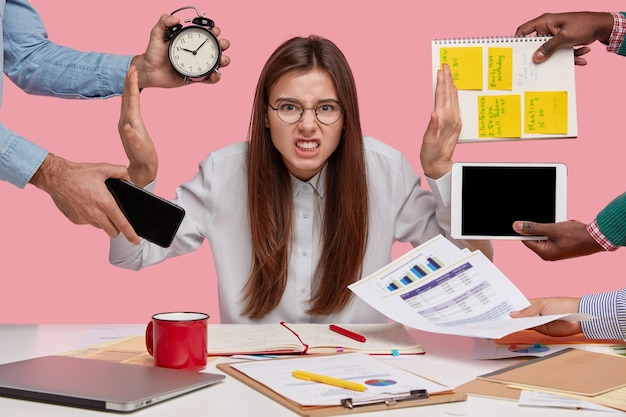 Überarbeiteter junger angestellter lehnt alles ab, runzelt verärgert die stirn, sitzt mit papierdokumenten und notizblock am schreibtisch, isoliert über der rosa wand. arbeitnehmerin stört sich an vielen fragen