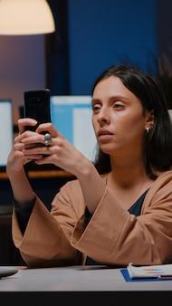 Überarbeiteter leitender manager, der marketingideen per telefon-sms hält und social media-strategien analysiert